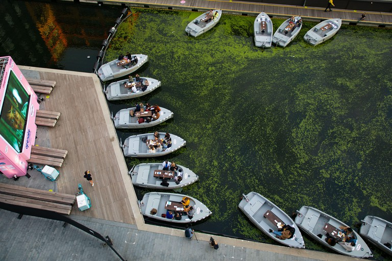 EDITORIAL USE ONLY An audience watches a film at the Openaire Float-In Cinema by H??agen-Dazs, which consists of a fleet of eco-boats providing seating for up to 128 people at Paddington Basin, London.