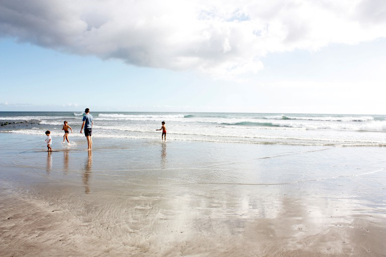 A young family play on the beach at Maspalomas, Gran Canaria, Canary Islands.Their shapes reflected in the shallow water.