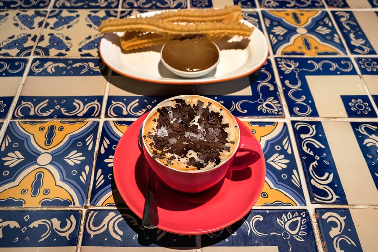 A cappuccino red cup with a plate with churros and dulce de leche - caramel on a coffee shop table