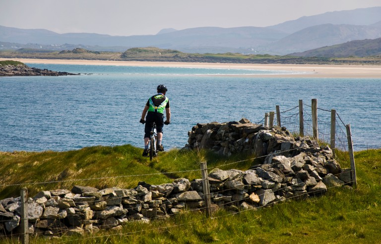 Man on mountain bike cycles by Atlantic Ocean coastline in Donegal