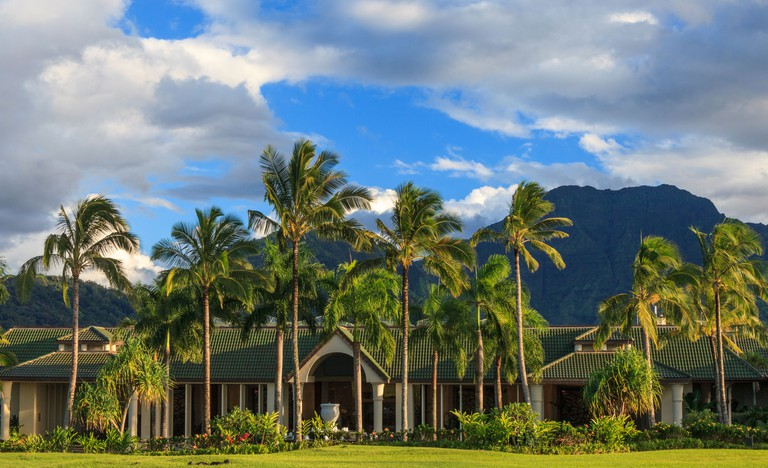 Entrance to the St. Regis Princeville Resort, with mountains with waterfall in distance