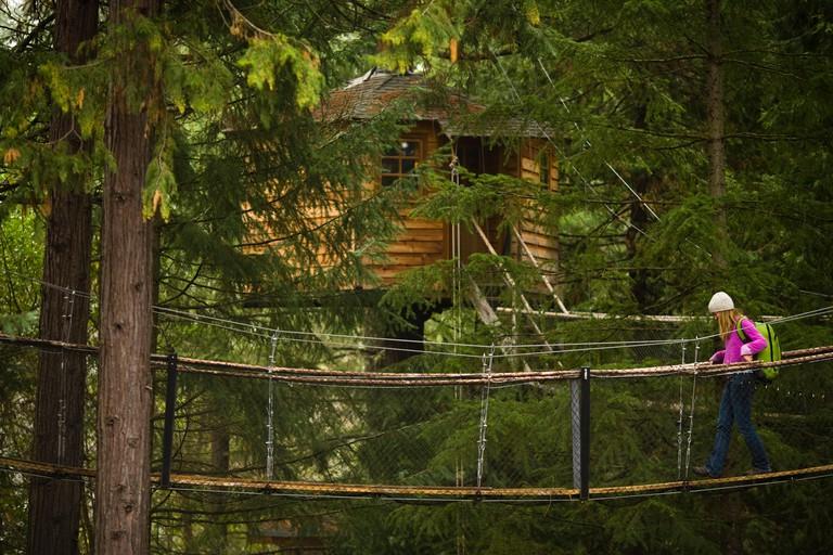 Adult woman walking a bridge at tree resort