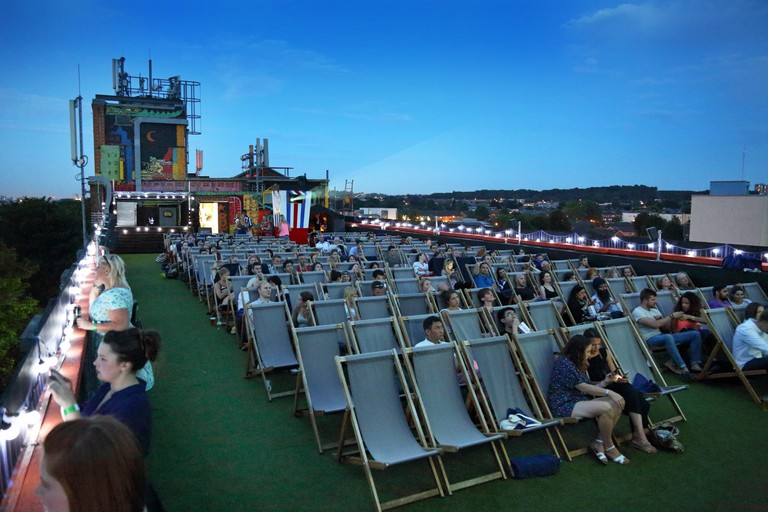 The open-air cinema on the roof of Peckham's Bussey Building. An audience enjoys John Travolta in Saturday Night Fever