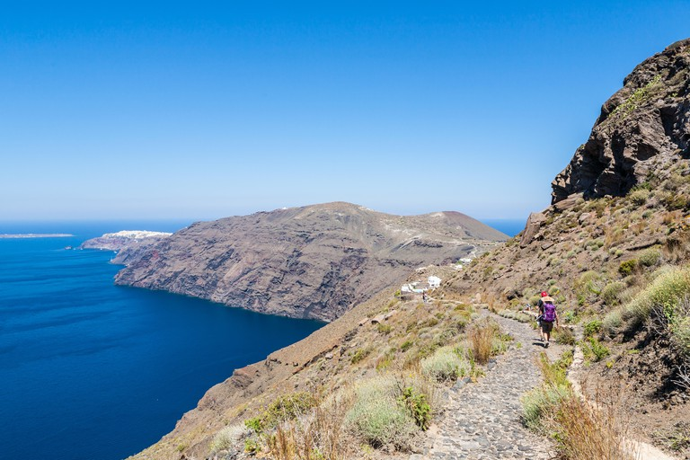 Couple hiking along the volcano rim from Fira to Oia on the Greek island of Santorini on a bright warm sunny day