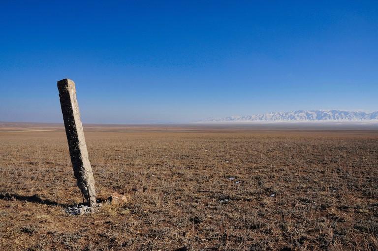 View across the desolate Kazakh steppe towards snow-capped mountains.