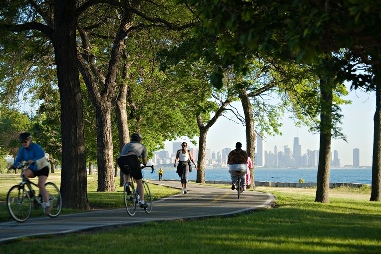 ILLINOIS Chicago Runners and bicyclists use paved path among trees along lakefront on summer morning skyline in distance