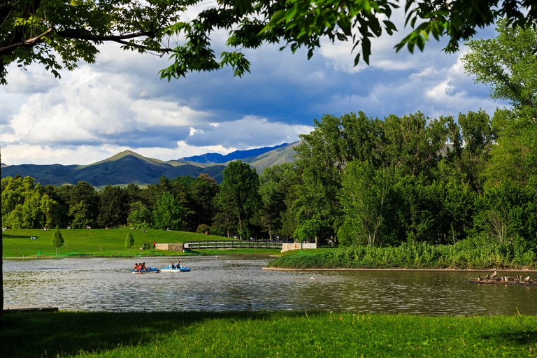 In this shot people paddle the paddle boats in the pond at Liberty Park in Salt Lake City, Utah, USA.