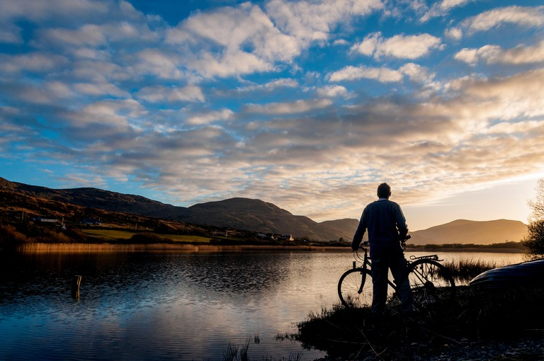 Ardara, County Donegal, Ireland weather. April 7th 2018. A cyclist stops to watch the sun go down over Lake Shanaghan after a warm, sunny day on Ireland's west coast. Credit: Richard Wayman/Alamy Live News