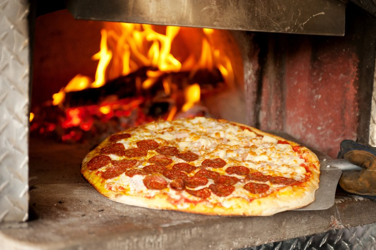 A pepperoni pizza cooks in a wood fired pizza oven.