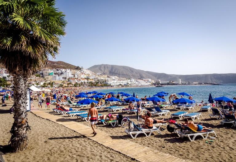 People sunbathing on the popular resort Playa de Las Americas in Tenerife