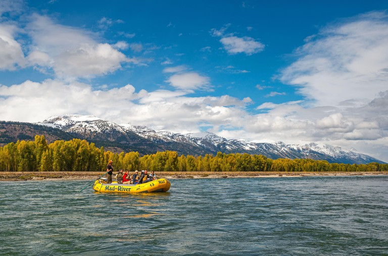 People rafting on the Snake River with the Grand Teton range in the snow and National Park in the background in Wyoming state, USA.