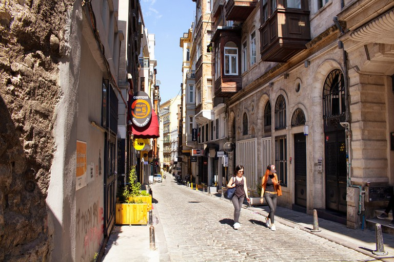 Two women walk on Serdar-i Ekrem street in Galata area of Beyoglu district in Istanbul on a sunny day. It's famous for design shops / stores, cafes.