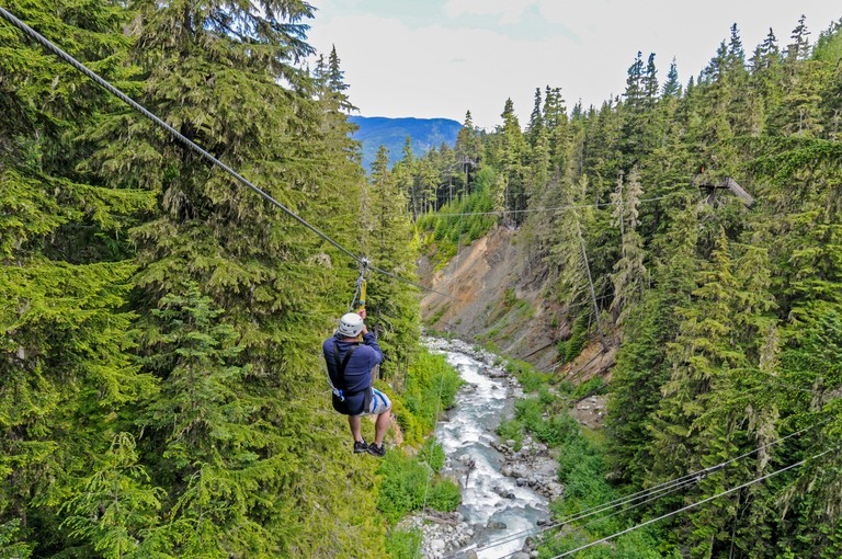 A tourist takes a higher and faster ride on the zip wire above the rushing waters at Fitzsimmons Creek in the steep wooded Blackcomb and Whistler mountain slopes near Whistler in British Columbia, Canada. There are approx five zip wire crossings, some suspended over 7,000ft above ground.