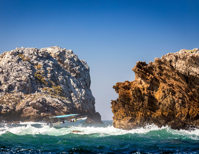 A tour boat shoots througha narrow channel of the Marietas Islands off the Pacific Coast of Nayarit, Mexico.