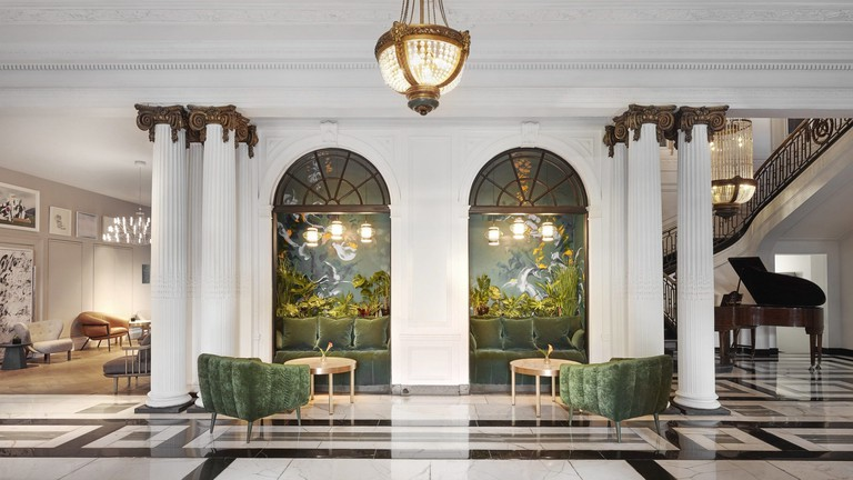 Lobby of Kimpton Blythswood Square Hotel featuring marble columns and green velvet chairs