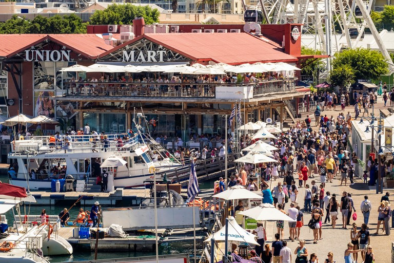 V&A Waterfront, and Cape Union Mart in Cape Town city, South Africa busy with people shopping in summer