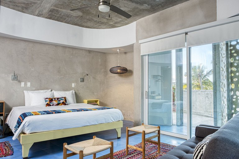 Minimalist double bedroom in El Blok with concrete walls, white linen, and double doors out to balcony
