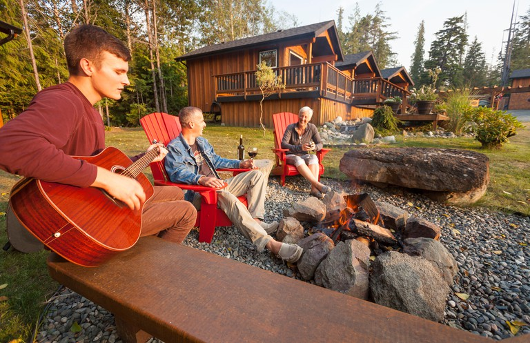 Friends gather around a fire while staying at the Ecoscape Cabins facility located in Port Hardy