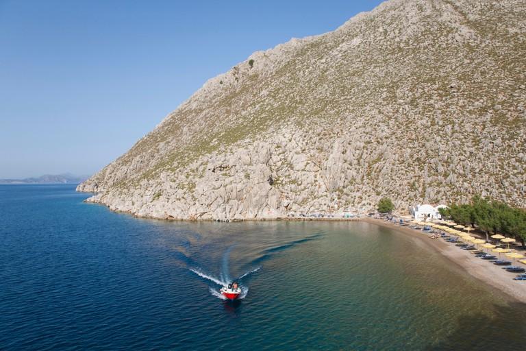 Pedi, Symi, South Aegean, Greece. Boat speeding across the sheltered cove of Agios Nikolaos.