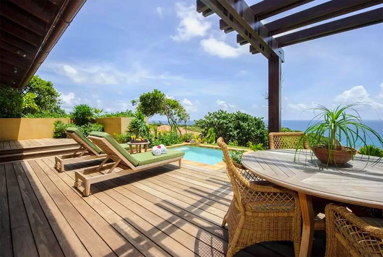 Deck at Royal Isabela with sun loungers, wicker chairs, plunge pool and oceanviews