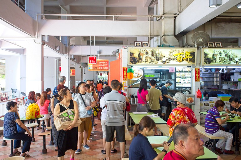 People queue up and eat food in a hawker centre in Singapore