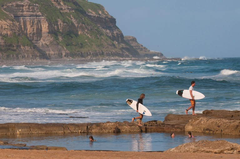 Surfers carry their boards over the rocks to open water at Bar beach Merewether, Newcastle, New South Wales, Australia.