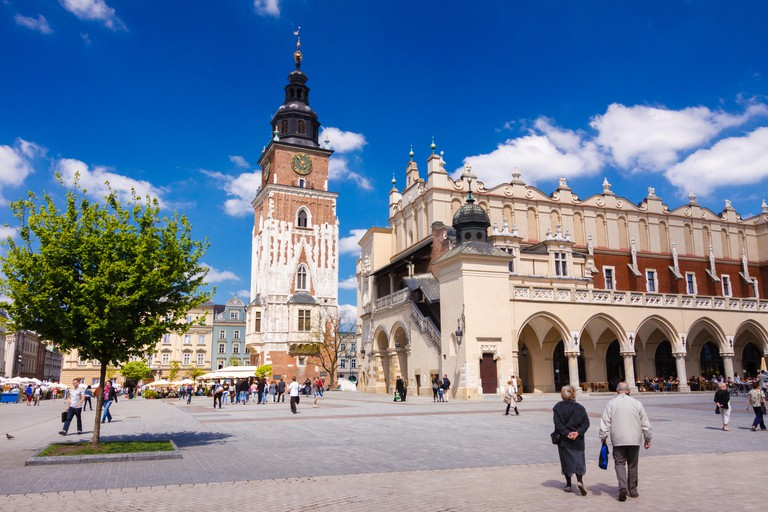 Krakow, Poland : People walks towards the Cloth hall building and old Town Hall Tower at the center of the main market square in the Krakow Old Town (