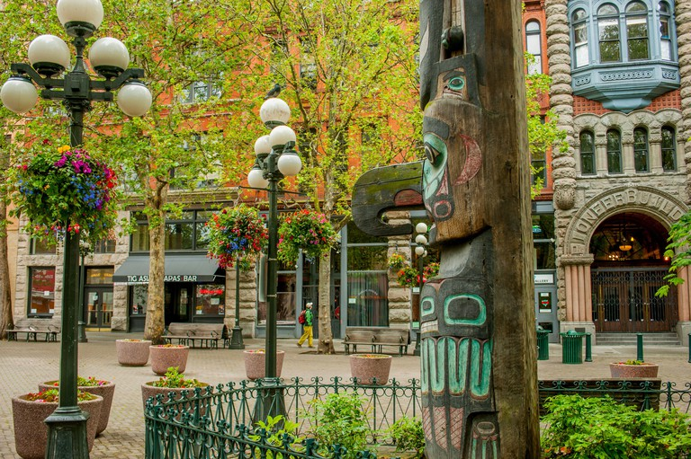 A totem pole with the Pioneer Building in the background on Pioneer Square in Seattle in Washington State, USA.