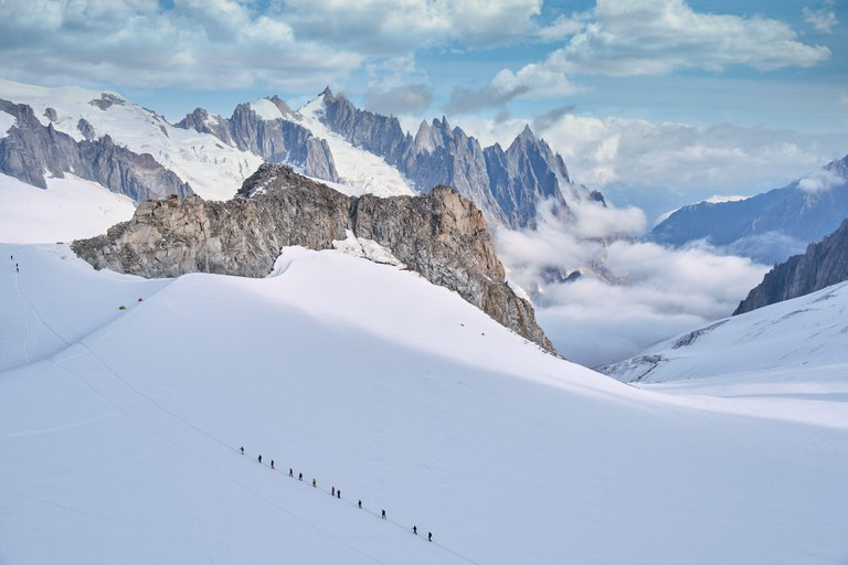 Many mountaineers roped together to ascend a glacier in Mount Blanc,  Courmayeur, Italy