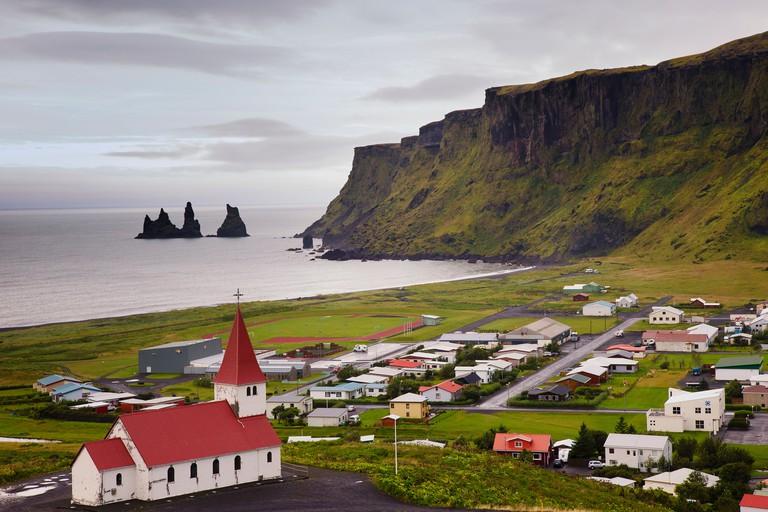 Aerial view over Vik (vik i myrdal) with its church and the reynisdrangar (basalt sea stacks) at dawn, South Iceland