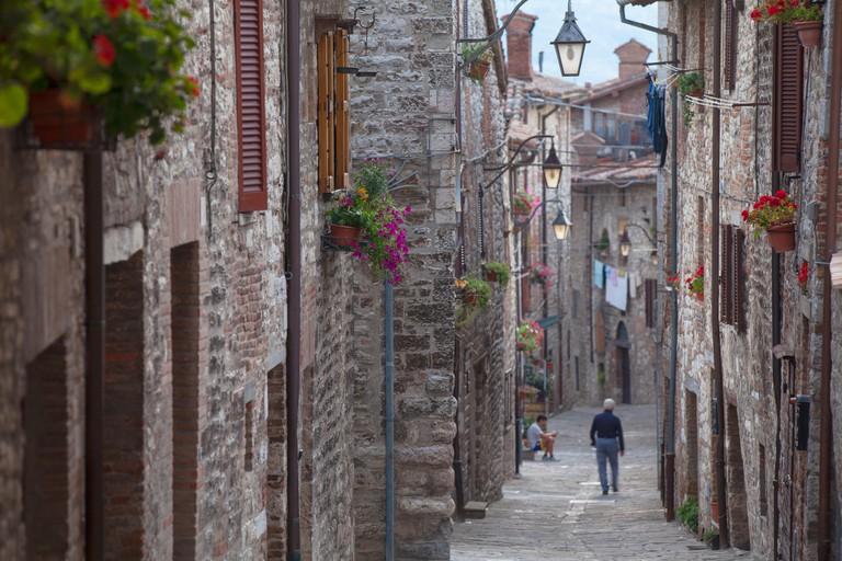 Man walking along Via Aquilante, Gubbio, Umbria, Italy, Europe