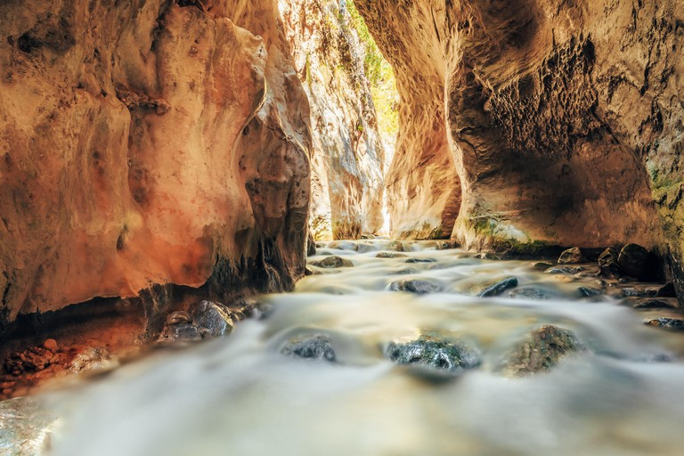 Popular tourist route In river bed Rio Chillar River In Nerja, Malaga, Spain. Water flow, slow motion.