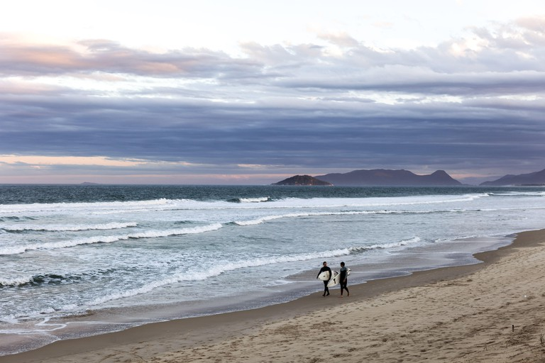 Surfers in Joaquina Beach at dusk. Image shot 06/2009. Exact date unknown.