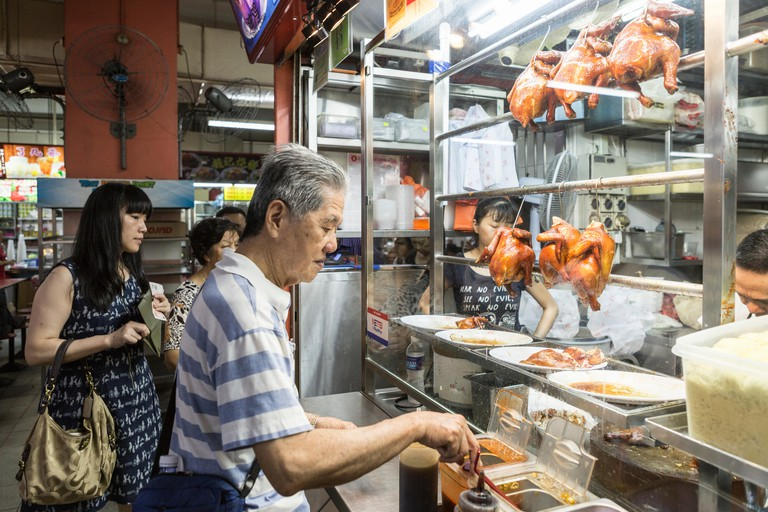 Customers line up at the Michelin starred Hong Kong Soya Sauce Chicken Rice and Noodle stall in the China Town Complex in Singapore