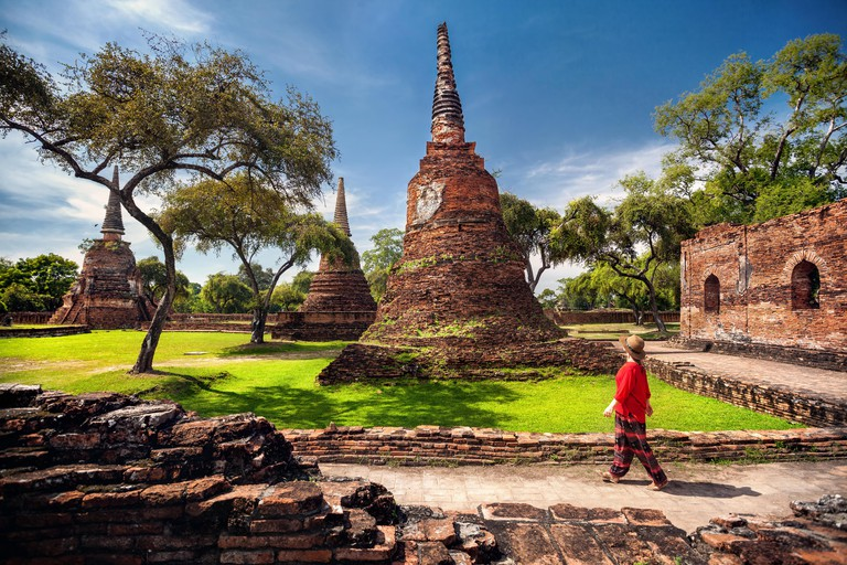Tourist Woman in red costume looking at ancient ruined stupas in Ayutthaya Historical park, Thailand