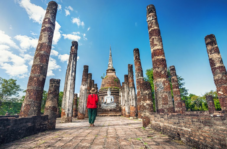 Tourist Woman in red costume looking at ancient Buddha statue in Wat Sa Si of Sukhothai Historical Park, Thailand