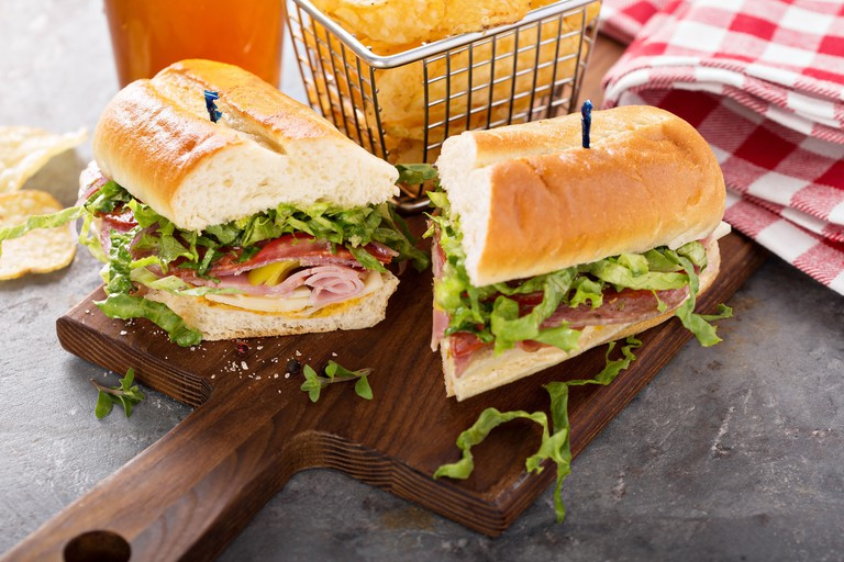 Italian sub sandwich with salami, ham and chips