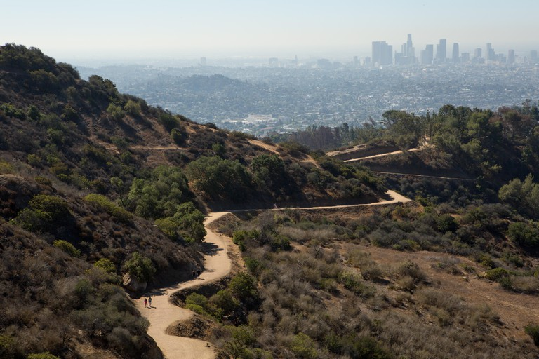 Hikers follow a winding path in the Hollywood Hills. Air pollution hangs over Los Angeles.