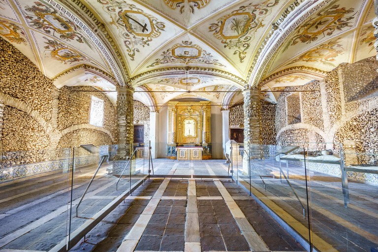 Spacious interior with bone-laid walls and frescoes on the ceiling, Chapel of Bones in Royal Church of St. Francis, Evora, Alentejo, Portugal
