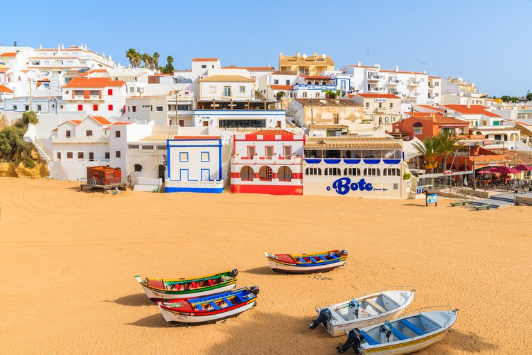 Fishing boats on beach in Carvoeiro village with colorful houses. Algarve region is popular holiday destinat