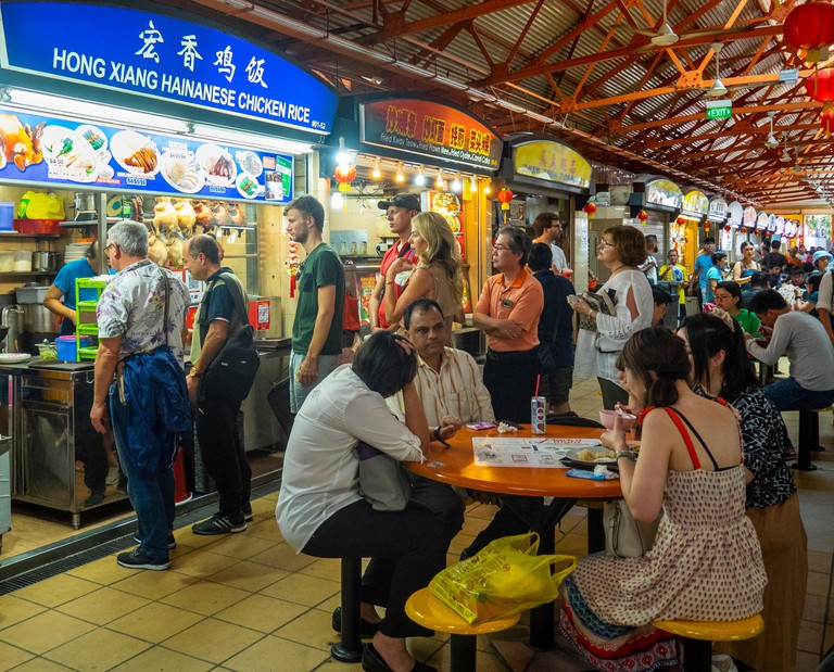 People, locals queuing for Hainanese chicken rice at Maxwell Food Centre a hawkers food hall in Tanjong Pagar Singapore.
