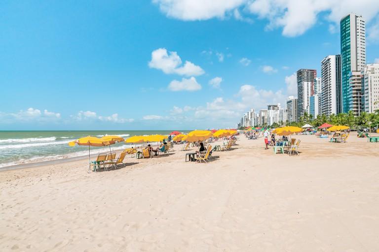 Recife, Boa Viagem Beach, Pernambuco, Brazil - June, 2019: Blue sky day at the beach with yellow umbrellas
