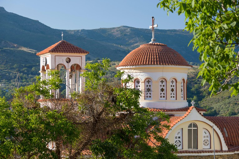 Elos, Chania, Crete, Greece. Bell-tower and dome of the Greek Orthodox church framed by trees.