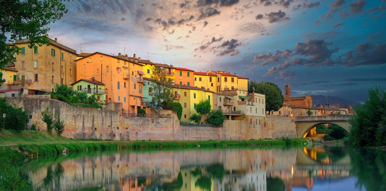 Old italian city Umbertide near Tevere river with cloudy sunset light