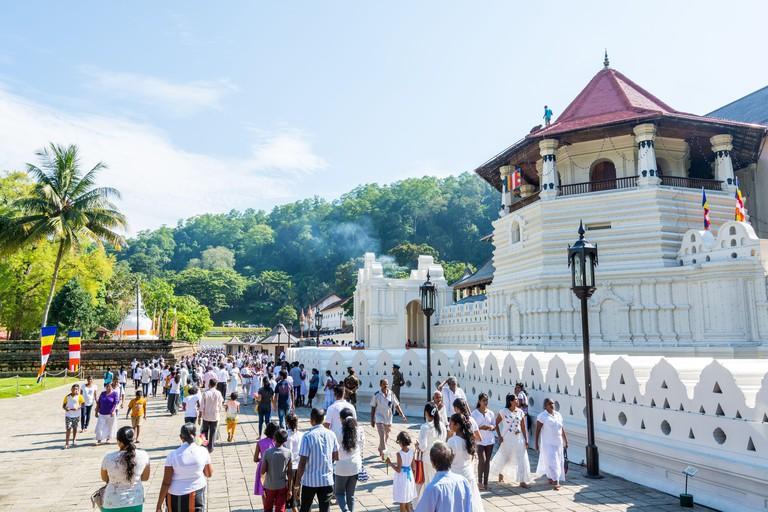 Buddhist pilgrims walking into the shrine of Sri Dalada Maligawa or the Temple of the Sacred Tooth Relic, in Kandy, Sri Lanka, celebrating the the Ves