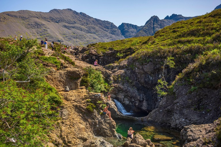 Glenbrittle, Scotland/UK-June 27, 2019: Vacationers swim in the Fairy Pools, which are cold swimmable pools, multiple waterfalls, that vibrant blue an