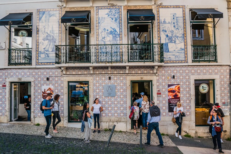 Tourists line up in front of the award winning pastry shop Pastelaria santo antonio in the Alfama area of Lisbon Portugal