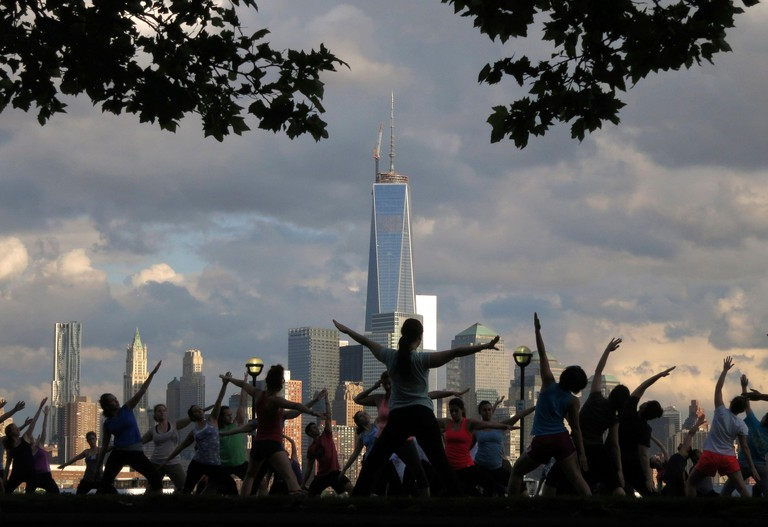 The Lower Manhattan skyline is seen in the distance during a weekly evening yoga class in a park along the Hudson River in Hoboken, New Jersey - 2CX2BFN