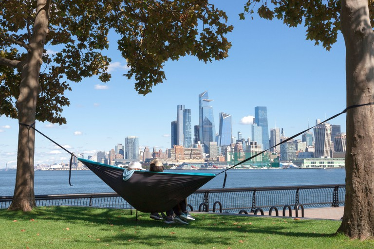Couple in hammock enjoying view of New York City/Manhattan skyline from across the Hudson River at Hoboken, New Jersey's waterfront. 2D1BXTR