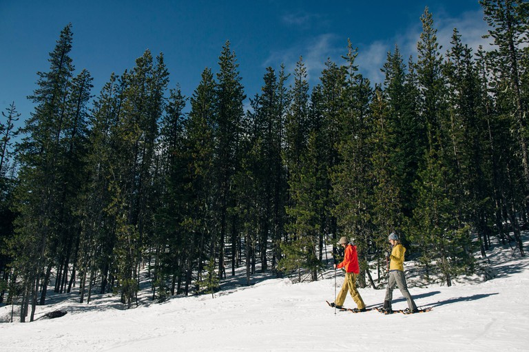 Two young women snow shoe on Mt. Hood on a sunny day.